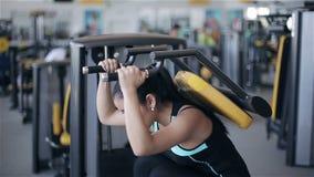Mujer asiática atractiva joven en el gimnasio Cantidad por el resbalador (carro) derecha a izquierda almacen de video