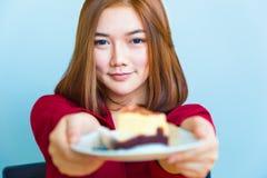 Mujer asiática atractiva joven feliz que sonríe y que da un pedazo o imagenes de archivo