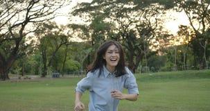 Mujer asiática atractiva joven que corre en un parque del verano en la puesta del sol Muchacha hermosa que disfruta de la natural almacen de metraje de vídeo