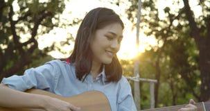 Mujer asiática atractiva joven que toca la guitarra acústica en un parque del verano metrajes