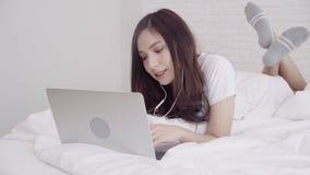 Mujer asiática atractiva que usa música del ordenador o del ordenador portátil y el escuchar mientras que miente en la cama almacen de video