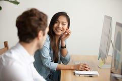 Mujer asiática atractiva sonriente que habla con el colega masculino en el trabajo Fotos de archivo