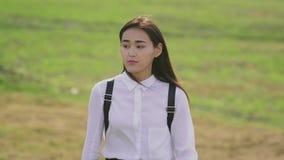 Mujer asiática bonita que va en el claro en la cámara lenta y persona que endereza el pelo almacen de metraje de vídeo