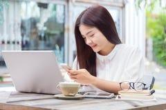 Mujer asiática casual joven feliz que usa tecnología en su ordenador portátil co Imagen de archivo libre de regalías