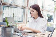 Mujer asiática casual joven que usa tecnología en su ordenador portátil Imagen de archivo libre de regalías