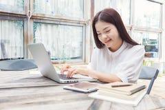 Mujer asiática casual joven sonriente feliz que usa tecnología en su l Fotografía de archivo