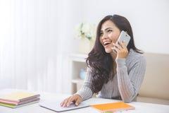 Mujer asiática casual que hace una llamada de teléfono en casa usando el teléfono elegante Foto de archivo libre de regalías