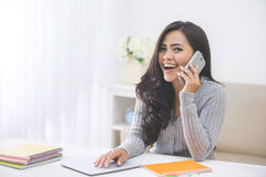Mujer asiática casual que hace una llamada de teléfono en casa usando el teléfono elegante Foto de archivo