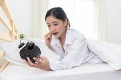 Mujer asiática chocada cuando despierte tarde cerca para olvidar a fijar la alarma foto de archivo libre de regalías