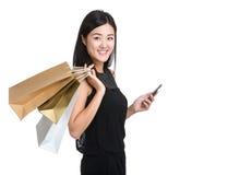 Mujer asiática con el panier y el teléfono móvil Imagenes de archivo