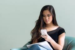 Mujer asiática con el pelo negro largo que mira el teléfono elegante mientras que TA Imagen de archivo