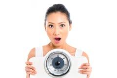 Mujer asiática con el peso perdidoso de la escala del peso Foto de archivo libre de regalías