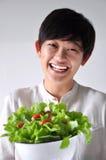Mujer asiática con la cara feliz que sostiene el cuenco de ensalada Fotos de archivo