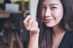 Mujer asiática con la cara sonriente que come la comida por la cuchara en café moderno Imagen de archivo