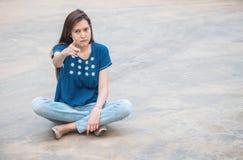 Mujer asiática con la emoción enojada de la cara en fondo concreto borroso de la textura del piso foto de archivo libre de regalías