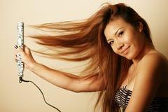 Mujer asiática con la enderezadora del pelo Fotografía de archivo libre de regalías