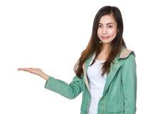 Mujer asiática con la mano que muestra con la muestra del balnk Fotografía de archivo libre de regalías