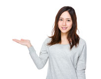 Mujer asiática con la palma abierta de la mano que muestra algo Imagen de archivo