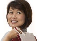 Mujer asiática con los bolsos de compras que miran para arriba fotos de archivo