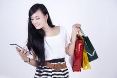 Mujer asiática con los bolsos de la tablilla y de compras del ordenador fotos de archivo