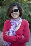 Mujer asiática con los vidrios de los ojos en camisa roja que sonríe en el parque Foto de archivo libre de regalías