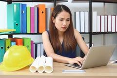 Mujer asiática confiada del ingeniero con el funcionamiento del ordenador portátil en el lugar de trabajo de la oficina foto de archivo libre de regalías