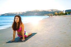 Mujer asi?tica de la aptitud joven en la playa que hace ejercicios de la base imagen de archivo libre de regalías