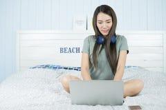 Mujer asiática de la belleza que se sienta en la cama y que juega el ordenador portátil en la cama para relajarse Imagenes de archivo