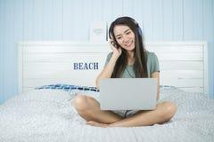 Mujer asiática de la belleza que se sienta en la música que escucha de la cama del auricular y que juega el ordenador portátil en Imagen de archivo