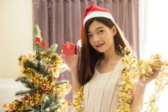 Mujer asiática de la sonrisa con el regalo de la Navidad Fotos de archivo