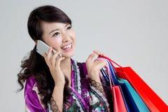 Mujer asiática de las compras que usa el teléfono elegante y sosteniendo los panieres coloridos Imagen de archivo