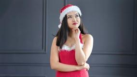 Mujer asiática de sueño bonita que lleva el traje de Santa Claus que sonríe y que presenta en el fondo gris del estudio