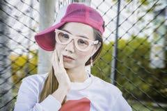 Mujer asiática del deporte del retrato en la ropa de deportes del rosa y blanca y llevar un sombrero, campo de fútbol interior pe fotos de archivo
