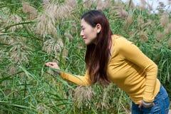 Mujer asiática del este que dobla sobre las flores de la cosecha Imagen de archivo