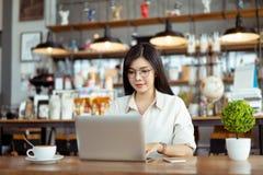 Mujer asi?tica del Freelancer feliz que trabaja usando el ordenador port?til digital foto de archivo libre de regalías