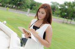 Mujer asiática del pelirrojo joven hermoso que lee un libro Imagen de archivo