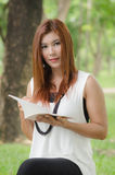 Mujer asiática del pelirrojo joven hermoso que sostiene un libro Imagen de archivo libre de regalías