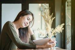 Mujer asiática del primer que lee un libro en el escritorio contrario de madera adentro Foto de archivo libre de regalías