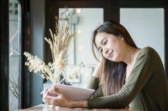 Mujer asiática del primer que lee un libro en el escritorio contrario de madera en cafetería con la cara feliz en backgroun borro Fotos de archivo libres de regalías