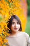 Mujer asiática del retrato que se coloca cerca de las flores amarillas. fotografía de archivo libre de regalías