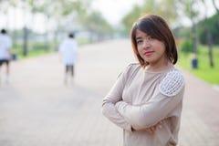 Mujer asiática del retrato que se coloca en parque. Foto de archivo