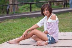 Mujer asiática del retrato que se sienta en una estera en la hierba fotos de archivo