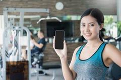 Mujer asiática deportiva hermosa que muestra smartphone con el app Imagen de archivo