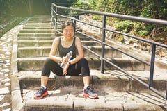 Mujer asiática deportiva que sienta el agua potable al aire libre de reclinación Fotografía de archivo