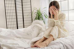 Mujer asiática deprimida que se sienta en cama Imágenes de archivo libres de regalías