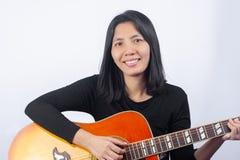 Mujer asiática divertida que toca la guitarra en el fondo blanco Fotos de archivo libres de regalías