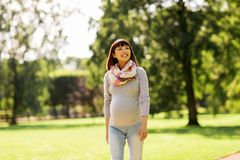 Mujer asiática embarazada feliz que camina en el parque imagenes de archivo