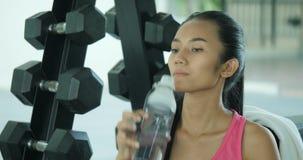 Mujer asiática en agua de la bebida del gimnasio después del ejercicio almacen de video