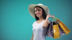 Mujer asiática en el sombrero del sol que lleva a cabo la suma grande de dólares y de muchos bolsos que hacen compras, préstamo almacen de metraje de vídeo