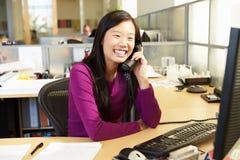 Mujer asiática en el teléfono en oficina moderna ocupada Fotografía de archivo libre de regalías